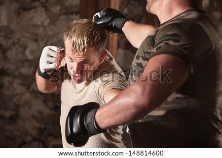 Blond MMA fighter dodges a punch and hits opponent - stock photo