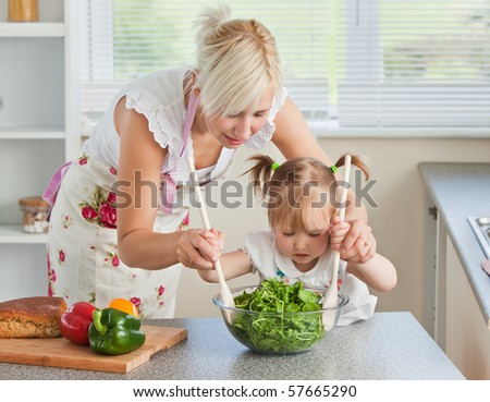 Blond mother and child cooking in kitchen - stock photo