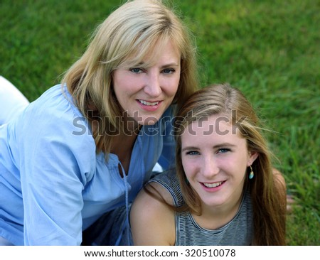 blond mother and daughter sitting in grass smiling