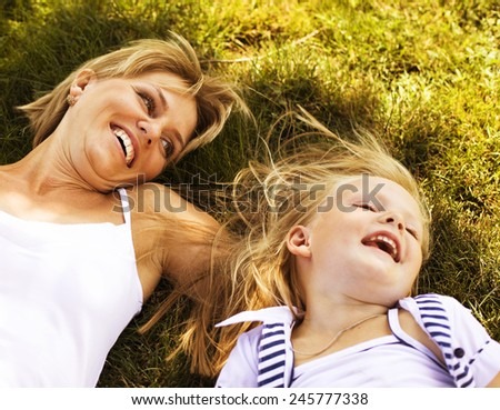 blond mother with daughter having fun on grass - stock photo