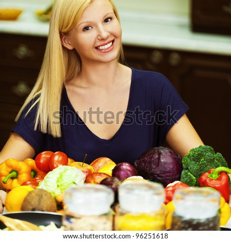 blond nice girl poses a smile while sitting at kitchen table littered with food (beets, cabbage, Bulgarian pepper, parsley, various cereals and pulses, plus a pan with already cooked food)