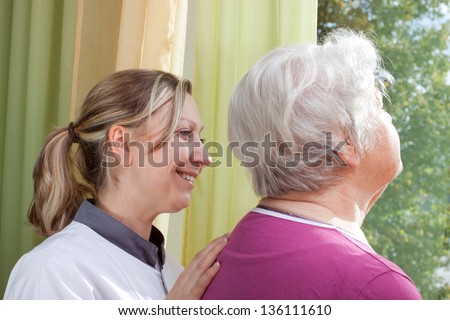 blond nurse and elderly woman standing at the window - stock photo