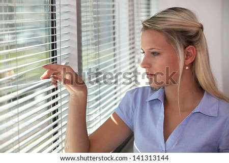 Blond office worker peering through window blinds - stock photo