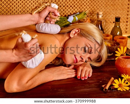 Blond pretty woman getting herbal ball  massage in tropical spa.