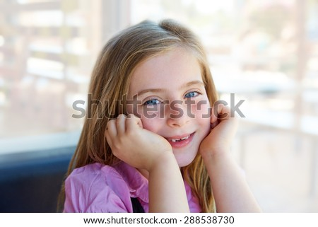 Blond relaxed happy kid girl expression blue eyes smiling - stock photo