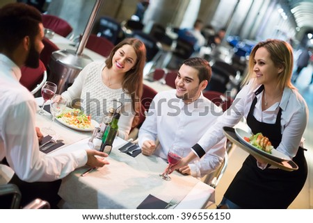 Blond russian  waitress bringing order at terrace table in summer day - stock photo