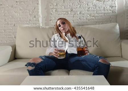 blond sad and wasted alcoholic drunk woman sitting at home sofa couch drinking scotch whiskey holding glass and bottle lonely and suffering hangover in alcoholism and alcohol abuse - stock photo