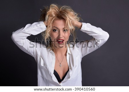 Blond sensual playful sexy woman with fashion makeup, red lips, portrait in white man shirt, posing with hands in hair studio photo