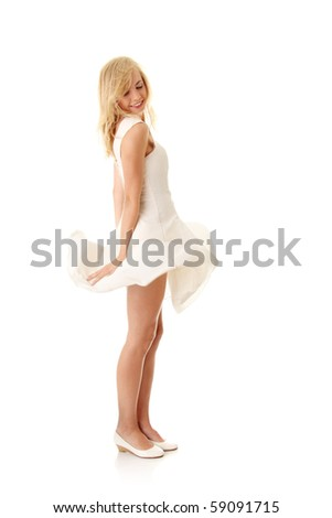 Blond sexy woman in white skirt blown by wind, isolated on white background
