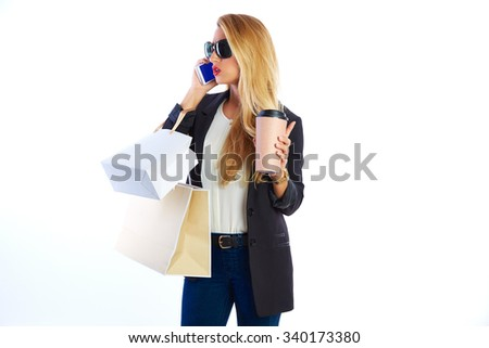 Blond shopaholic woman with bags talking with smartphone on white background