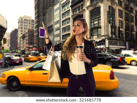 Blond shopping tourist girl calling a yellow Taxi in New York fifth avenue Photomount - stock photo
