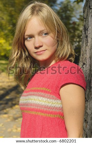 blond smiling girl in the autumn park