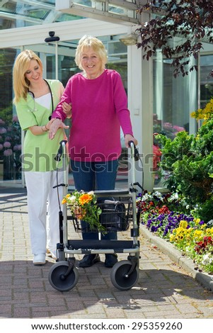 Blond Smiling Nurse Holding Arm of Senior Woman with Walker  Helping Senior Resident to Walk Outdoors in front of Building Entrance Near Flower Beds. - stock photo