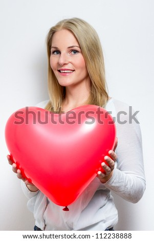 Blond ^Smiling Woman Holding a Heart Balloon - stock photo