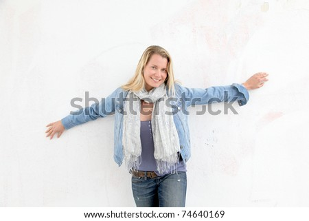 Blond smiling woman leaning against wall - stock photo