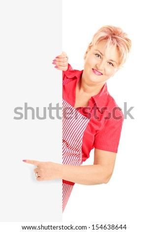 Blond smiling woman wearing an apron and gesturing on a blank panel isolated on white background - stock photo