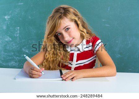 Blond student girl writing notebook at class green chalk board sitting in desk - stock photo
