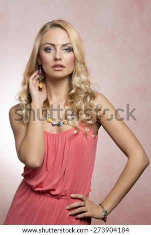 blond summer young woman in pink dress , with curly hairstyle , posing with jewellery - stock photo