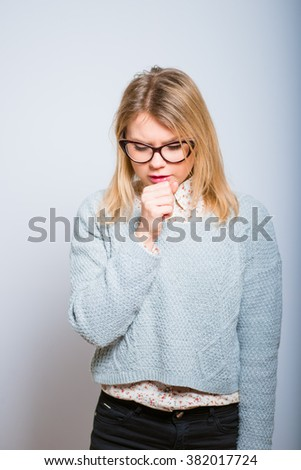 blond sweet girl is sick and is coughing, wearing glasses isolated on a gray background - stock photo