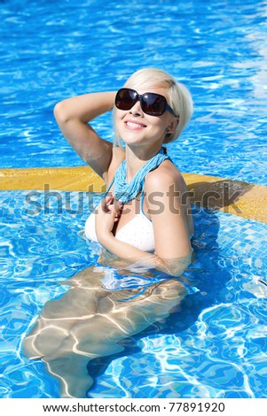 Blond swimming in a clear pool