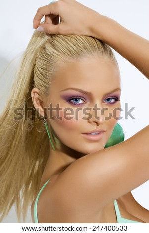 Blond tanned girl posing joyfully.