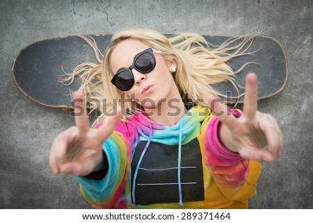 Blond teen skater girl giving peace sign - stock photo
