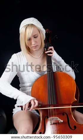 Blond teenage girl musician playing a cello