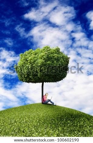 blond teenager girl sitting under a tree with laptop - stock photo