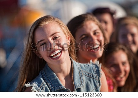 Blond teenager with friends laughing outdoors - stock photo