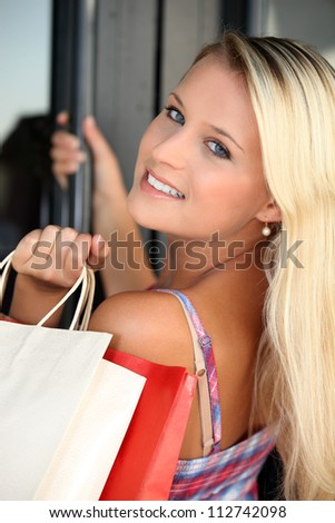 Blond teenager with shopping bags - stock photo