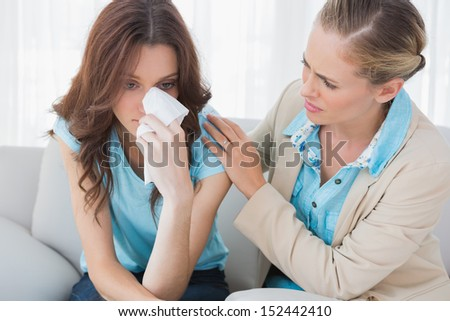 Blond therapist looking at her patient crying on sofa in office