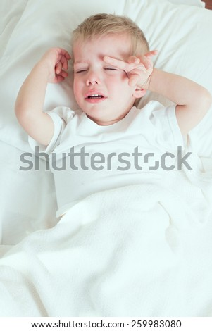blond toddler boy boy  crying in bed  - stock photo