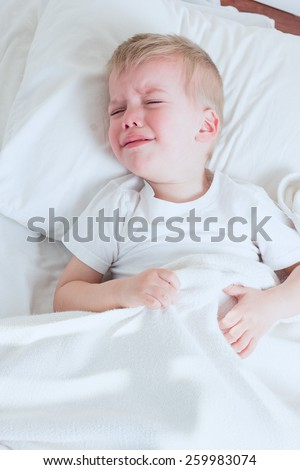 blond toddler boy crying in bed  - stock photo