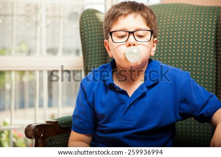 Blond tween with glasses blowing a bubble with some chewing gum at home - stock photo