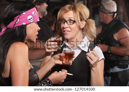 Blond woman and biker gang lady talking while smoking and drinking
