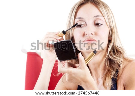 blond woman applying eye shadow to her eyes - stock photo