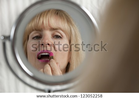 Blond woman applying red lipstick in mirror - stock photo