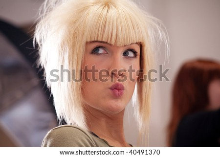 blond woman at hairdresser with funny face expression, indoor shot - stock photo