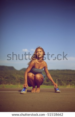 Blond woman barefoot on a road - stock photo