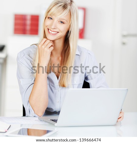 Blond woman browsing the internet using her laptop - stock photo
