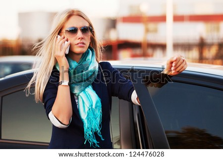 Blond woman calling on the phone against a car - stock photo