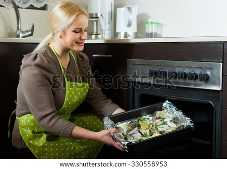 Blond woman cooking fish  in oven at home kitchen
