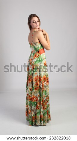 Blond woman dressed a colorful long dress - stock photo