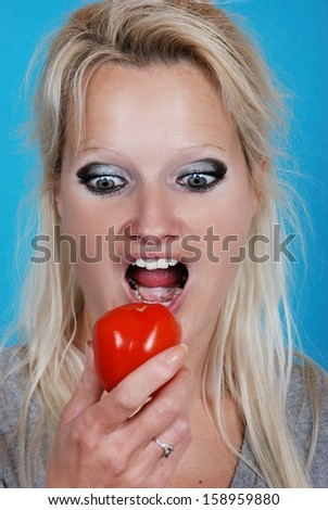 Blond woman eating a tomato