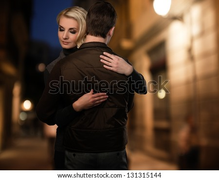 Blond woman embracing man in brown vest outdoors at night - stock photo