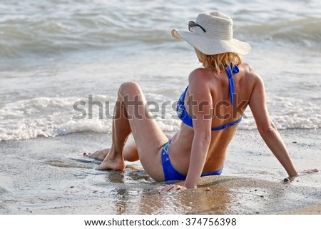 Blond woman enjoying the sea on the sand beach.