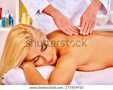 Blond woman getting massage in health resort. Eyes closed. - stock photo