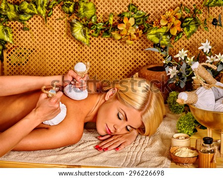 Blond woman getting massage in tropical spa. Eyes are closed.