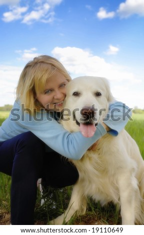 blond woman happy with her golden retriever dog