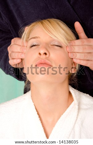 blond woman has headache and men hand massage her head